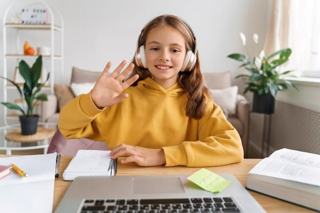 Улыбающаяся школьница делает видеозвонок с ноутбуком дома