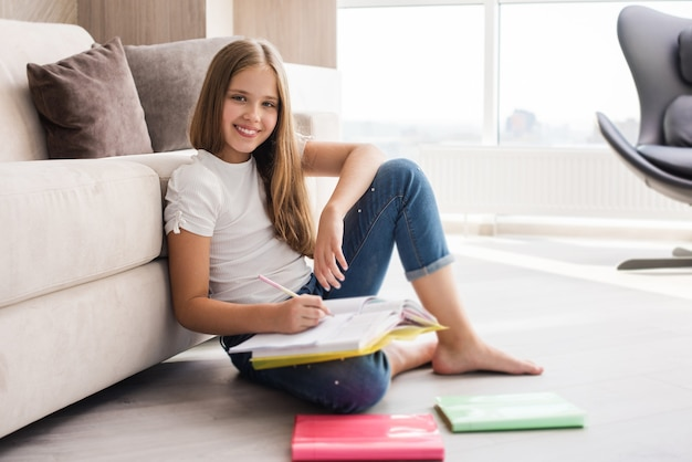 Smiling school girl sit on floor with notebooks