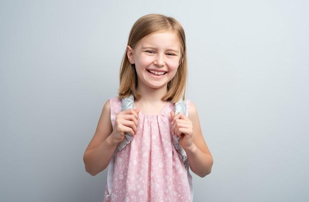 分離されたバックパックと笑顔の学校の女の子