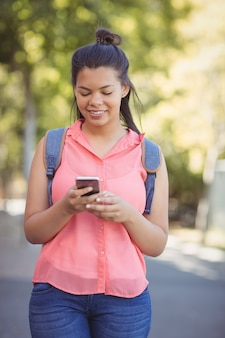 キャンパス内で携帯電話を使用してカバンを持つ女子高生の笑顔
