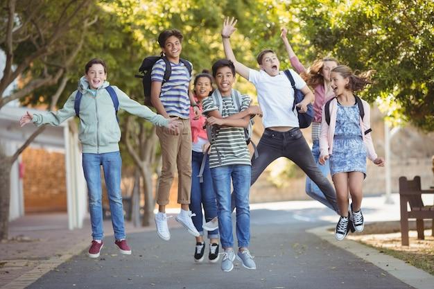 キャンパス内の道路で楽しい学校の子供たちの笑顔