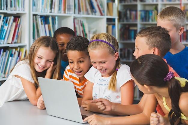 図書館でノートパソコンを見て笑顔の学校の子供たち