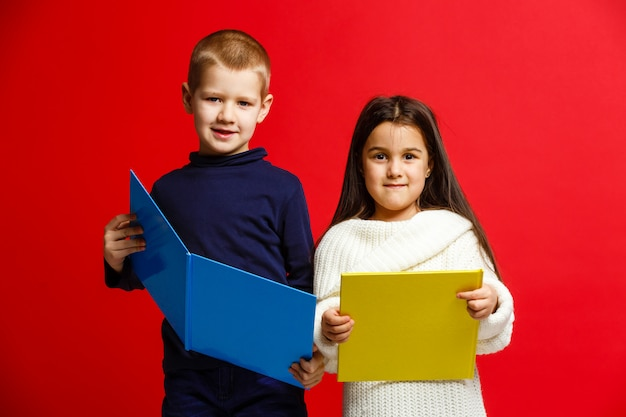 Smiling school kids reading a book isolated on red background