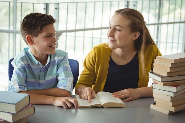 学校の図書館で本を読んで笑顔の学校の子供たち