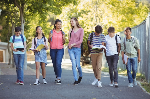 キャンパス内の道を歩いて笑顔の学校の子供たち