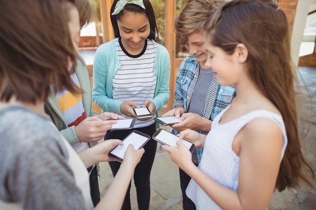 サークルに立って携帯電話を使用して笑顔の学校の生徒