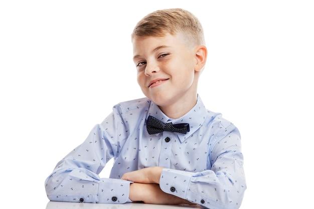 Улыбающийся школьник в голубой рубашке с бабочкой сидит за столом.