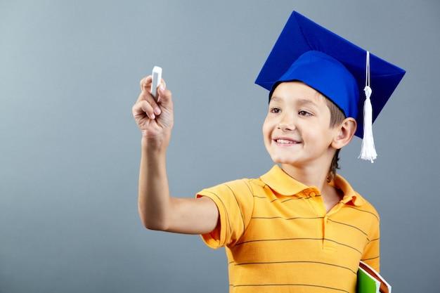 Улыбаясь школьник держит мел