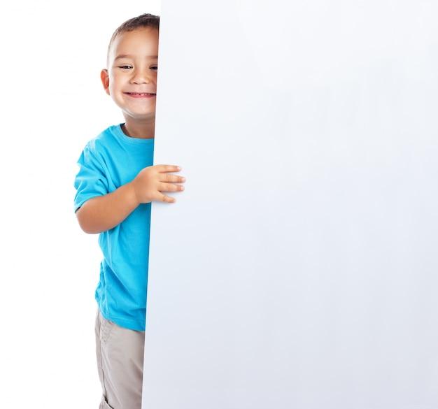 Scolaro sorridente in possesso di un cartello in bianco