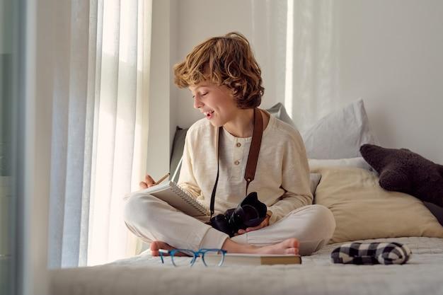 Улыбающийся школьник делает заметки в тетради, делая домашнее задание в помещении