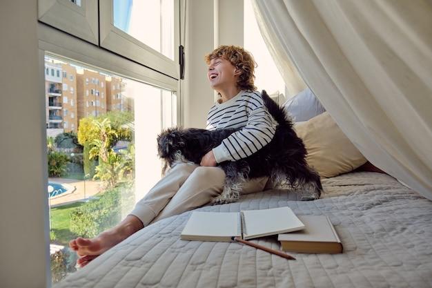 Улыбающийся школьник с ризеншнауцером, глядя в окно с кровати