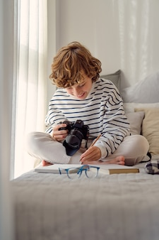 Улыбающийся школьник с фотоаппаратом на кровати дома