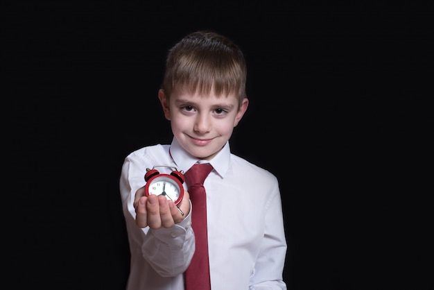 Smiling schoolboy with a red alarm clock in his hands.
