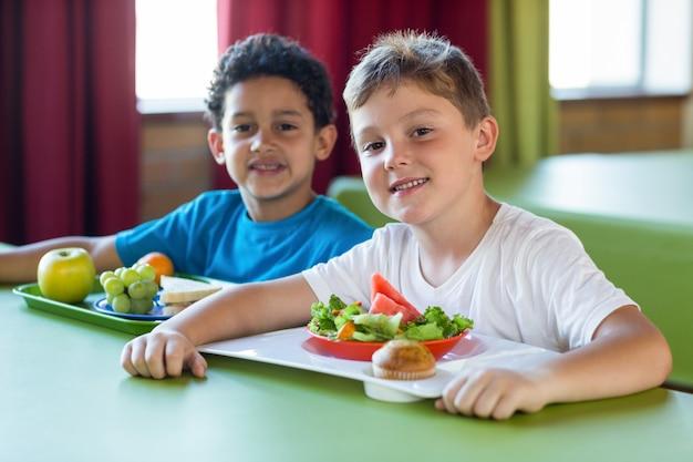 Smiling schoolboys having meal
