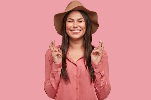 Улыбающаяся школьница полна желаний, держит пальцы скрещенными, широко улыбается
