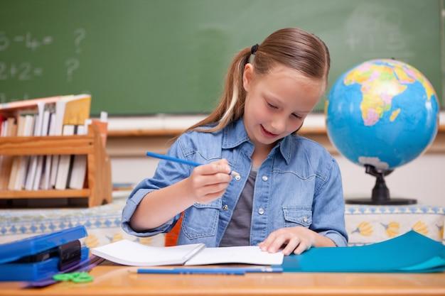Smiling schoolgirl doing classwork