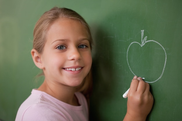 Smiling schoolgirl drawing an apple