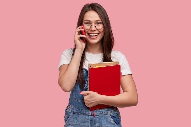 La studentessa sorridente ha una conversazione telefonica durante la pausa, tiene in mano il cellulare moderno, indossa una tuta di jeans, tiene il blocco note a spirale