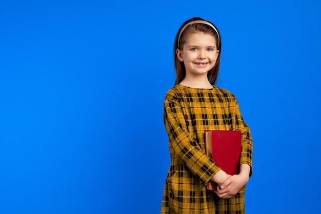 Улыбающаяся школьница в повседневном платье держит книги у синей стены
