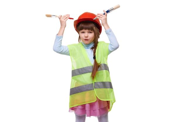 헬멧 및 건설 조끼에 웃는 여학생 격리 된 흰색 배경에 페인트 브러시와 재미