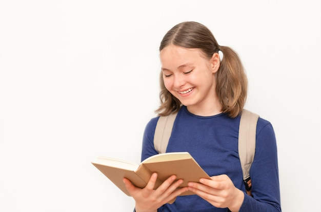 Smiling schoolgirl looking at the open textbook on the gray surface