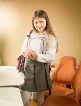 Улыбающаяся школьница позирует с книгами в своей спальне