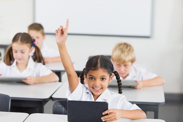 Улыбающаяся школьница поднимает руку в классе