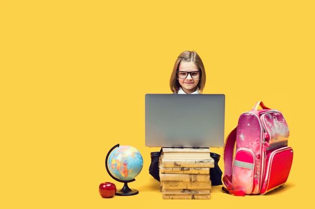 웃는 여학생은 책 더미 뒤에 앉아 글로브와 배낭 어린이 교육을 통해 노트북 작업을 합니다.