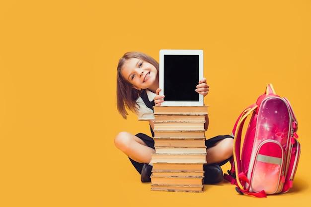 웃는 여학생은 책 더미 뒤에 앉아 태블릿이 카메라 어린이 교육을 바라보는 것을 보여줍니다.