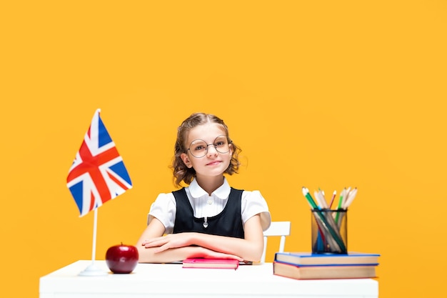 Smiling schoolgirl sitting at the desk with notebook during english lesson great britain flag