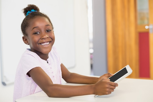 Smiling schoolgirl using digital tablet in classroom at school