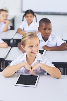 Улыбающаяся школьница с помощью цифрового планшета в классе