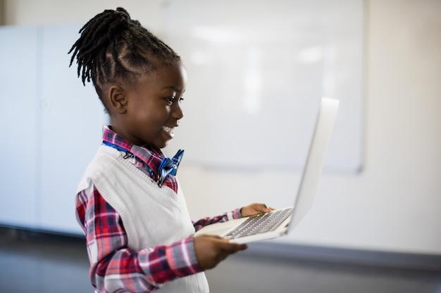 Smiling schoolgirl using laptop in classroom