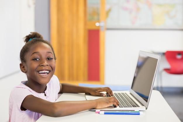 Smiling schoolgirl using laptop in classroom