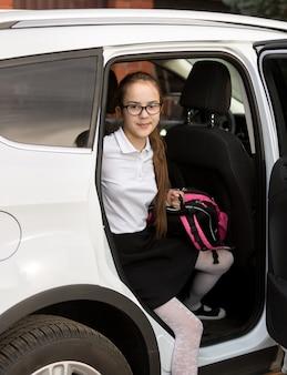 Улыбающаяся школьница с сумкой выходит из машины
