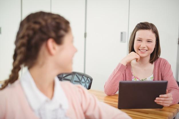 教室で友達に話しているデジタルタブレットで笑顔の女子高生