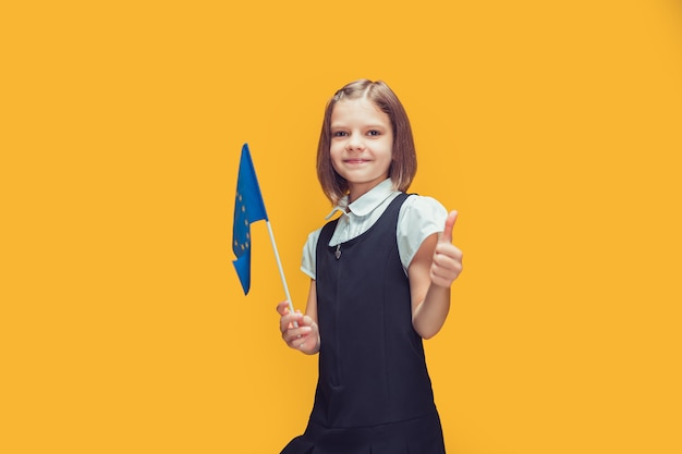 Smiling schoolgirl with small flag of european union showing thumbup education in europe concept