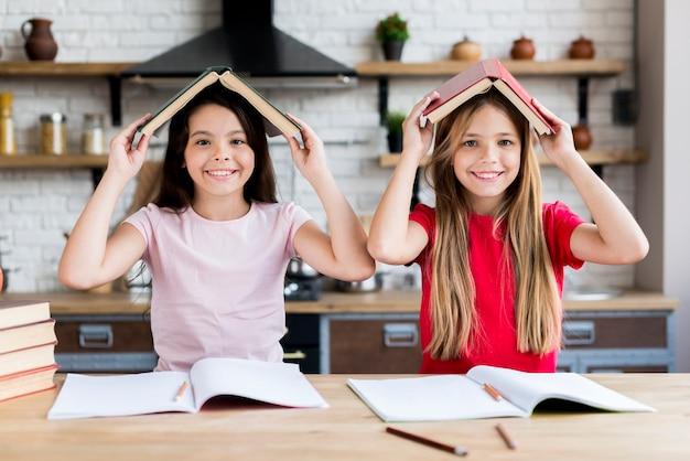 Smiling schoolgirls under book roof