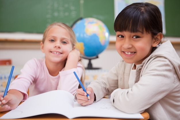 Smiling schoolgirls doing classwork