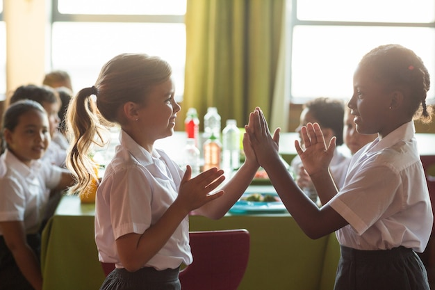 Smiling schoolgirls playing clapping game