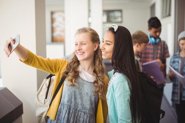 廊下で携帯電話でselfieを取って笑顔の女子学生