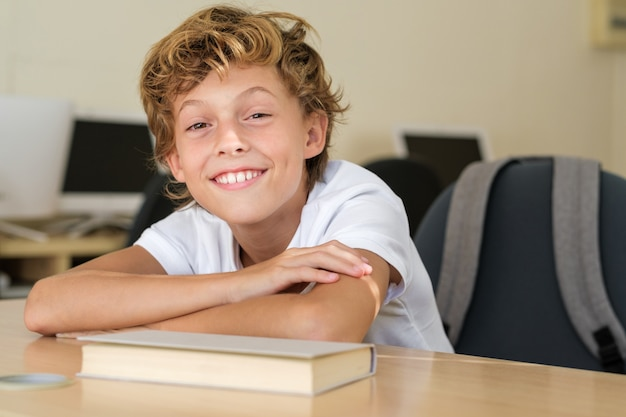 Smiling schoolkid sitting at table in classroom