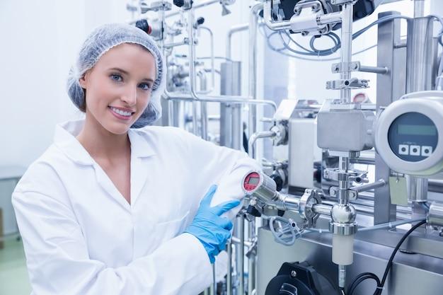 Smiling scientist leaning against gauge