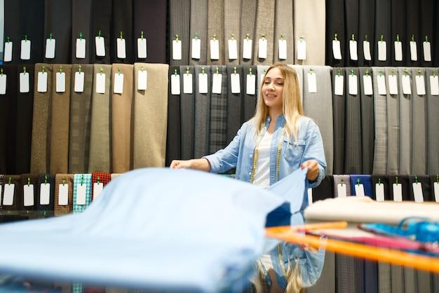 Улыбающаяся швея держит ткань в текстильном магазине. полка с тканью для шитья
