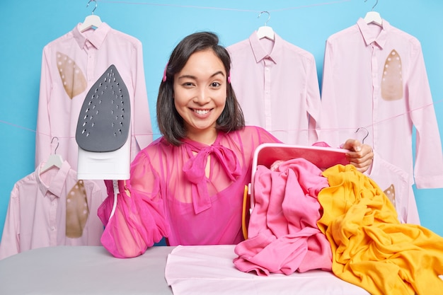 Smiling self confident housewife holds steam electric iron feels glad busy ironing laundry poses against ironed clothes. happy housekeeper has much work to do