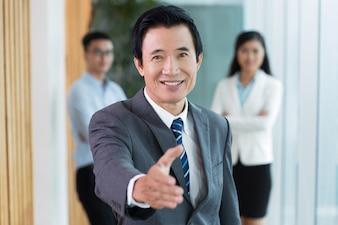 Smiling senior Asian businessman offering handshake