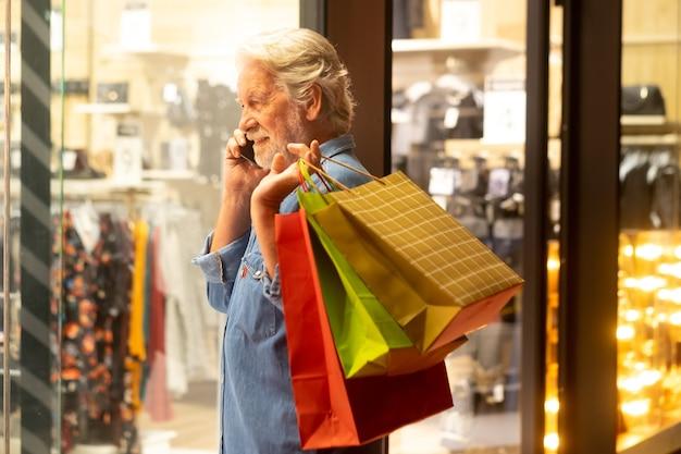携帯電話に話し、店の窓を見ながら買い物袋を持って笑顔のシニアひげを生やした男
