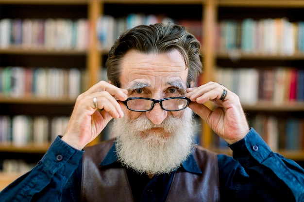 Smiling senior bearded man touching his eyeglasses, standing in library or book store over the blurred background of book shelves. close up portrait