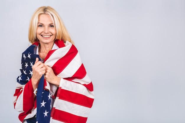 驚きの顔で白い背景の上に分離された米国旗を身に着けている笑顔のシニア美しい愛国心が強い女性。