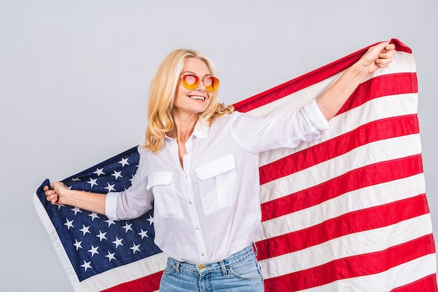 Smiling senior beautiful patriotic woman wearing united states flag isolated over white background with a surprise face.